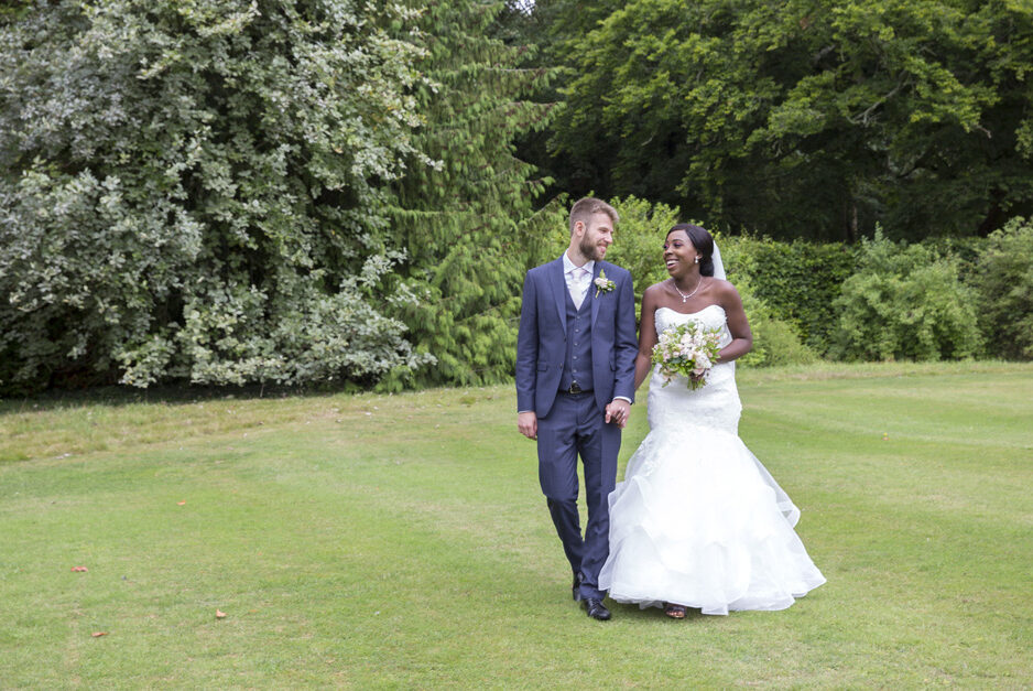 bride and groom holding hands walking around the grounds at Hartwell House in Buckinghamshire