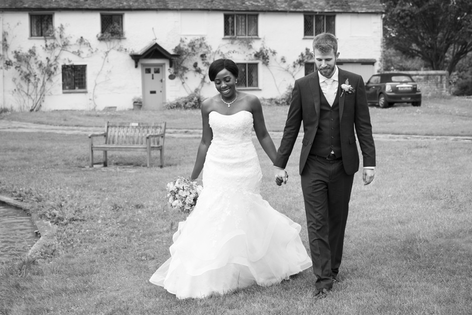 bride and groom walking around duck pond outside St Mary's Church in Haddenham, Buckinghamshire