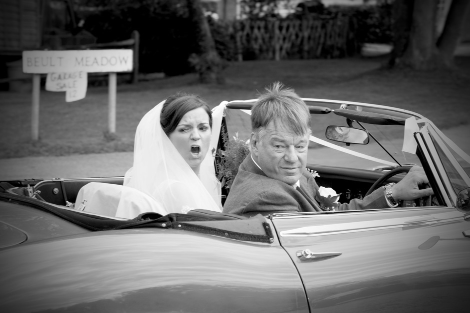 bride pulling shocked face pulling up with father in classic car at St Michael the Archangel Church wedding in Smarden, Kent