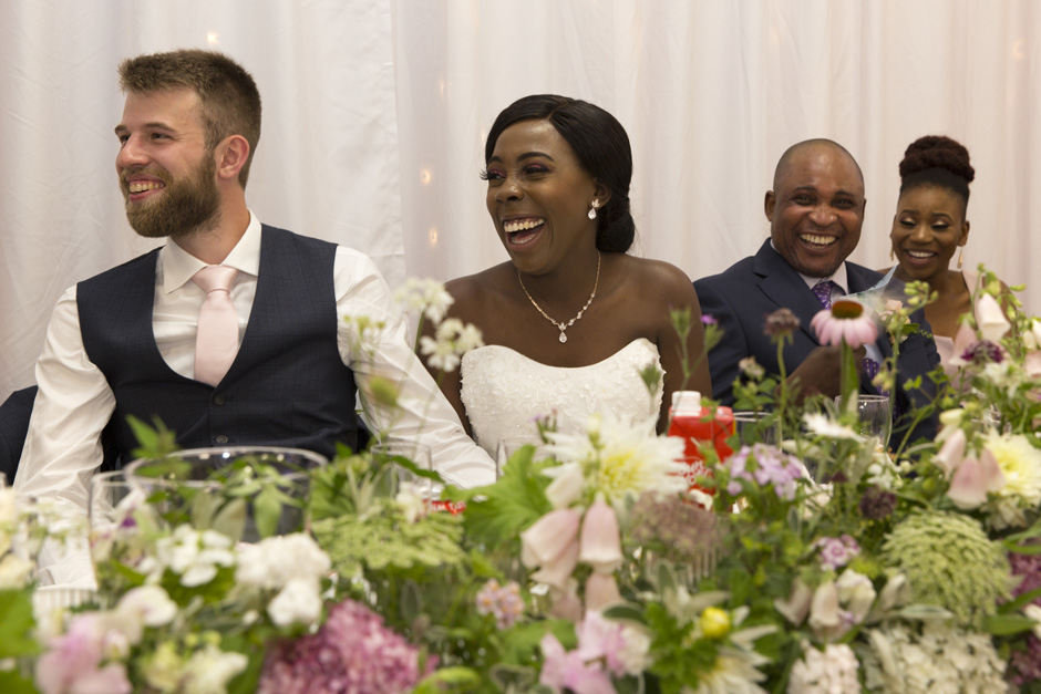 bride and groom with father of the bride and maid of honour laughing uncontrollably during wedding speeches at Haddenham Village Hall in Buckinghamshire