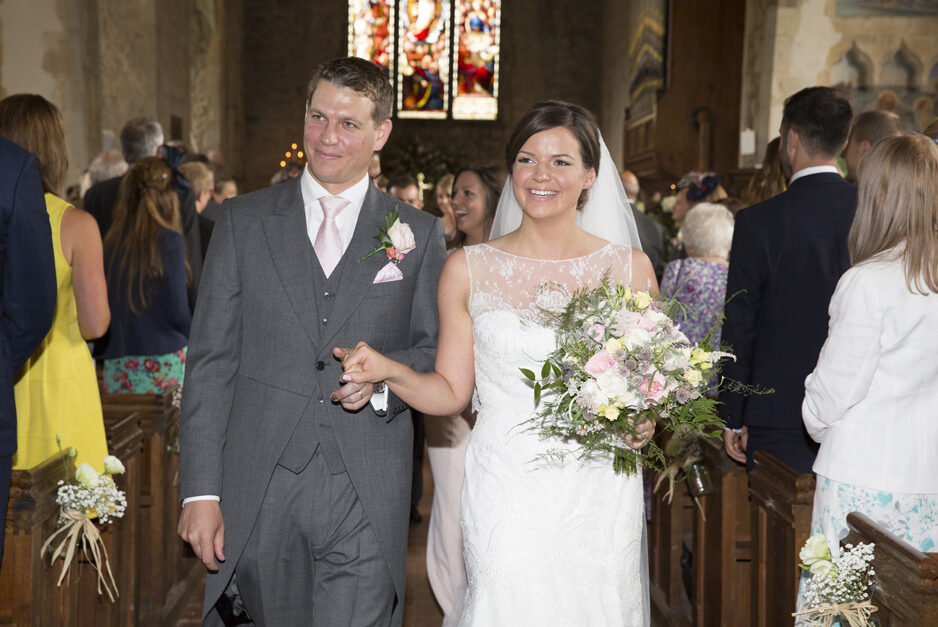 bride and groom walking up the aisle at St Michael the Archangel Church wedding ceremony in Smarden, Kent
