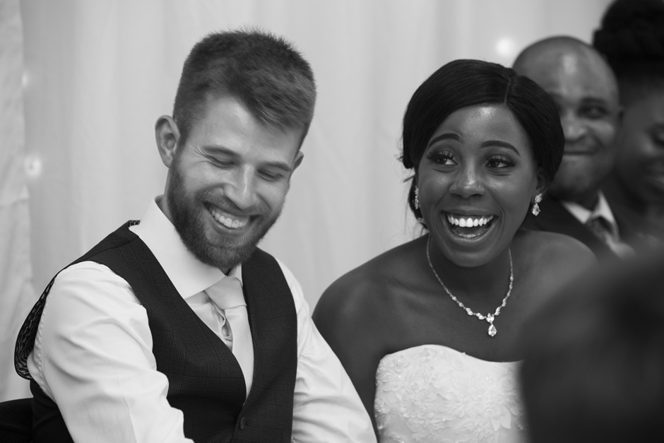 bride and groom laughing during wedding speeches at Haddenham Village Hall in Buckinghamshire