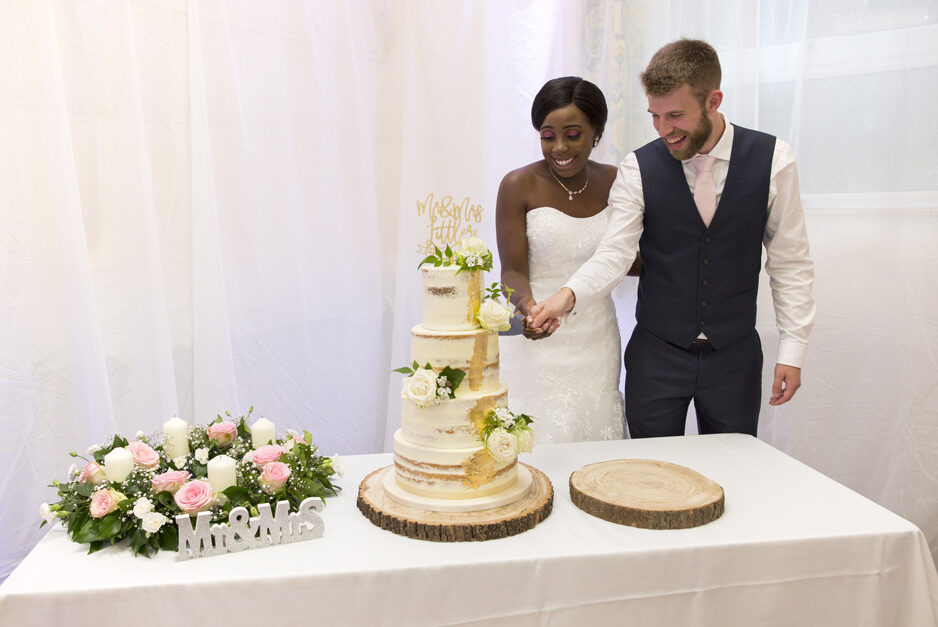 bride and groom cutting their four tiered wedding cake decorated with white rose and gold paint at Haddenham Village Hall in Buckinghamshire