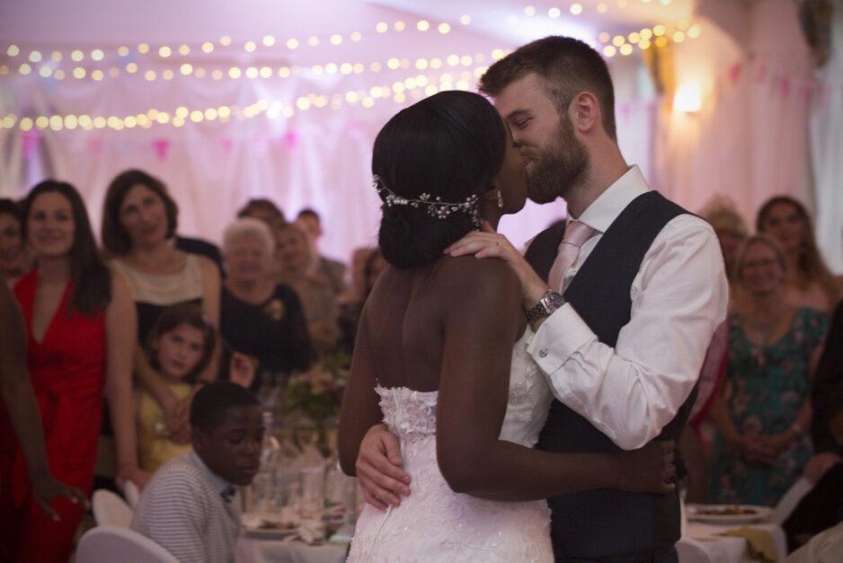 bride and groom kiss during their first dance at Haddenham Village Hall wedding reception in Buckinghamshire