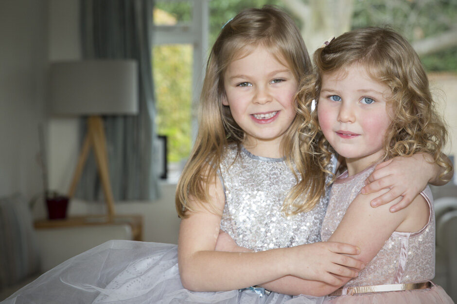 little girls holding each other in sparkly dresses in West Malling in Kent