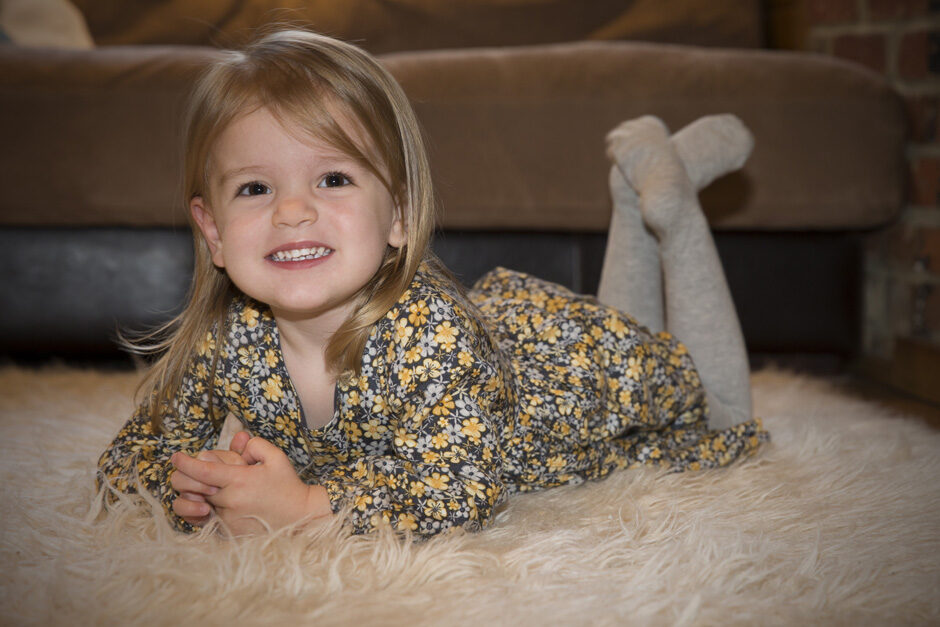 little girl smiling laying on her tummy in Plaxtol, Kent
