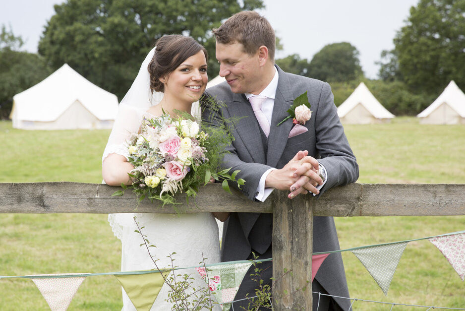 bride and groom portrait in front of yurts at Smarden village home wedding