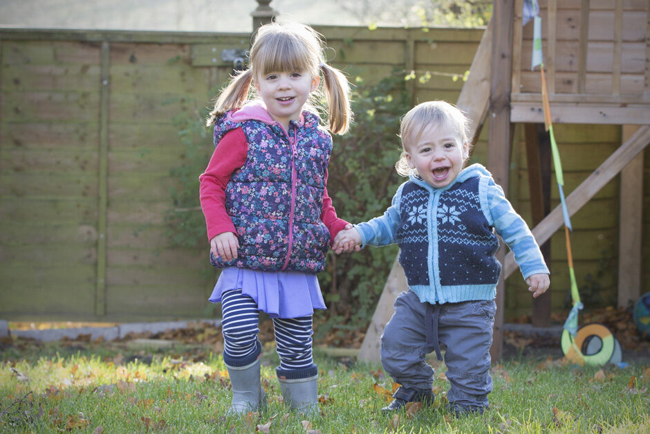 little girl with her toddler brother in their garden in Tonbridge, Kent