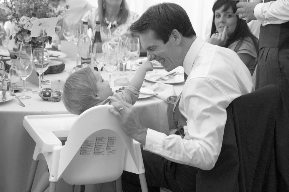 baby poking father's nose laughing at wedding breakfast at Smarden village marquee in Kent