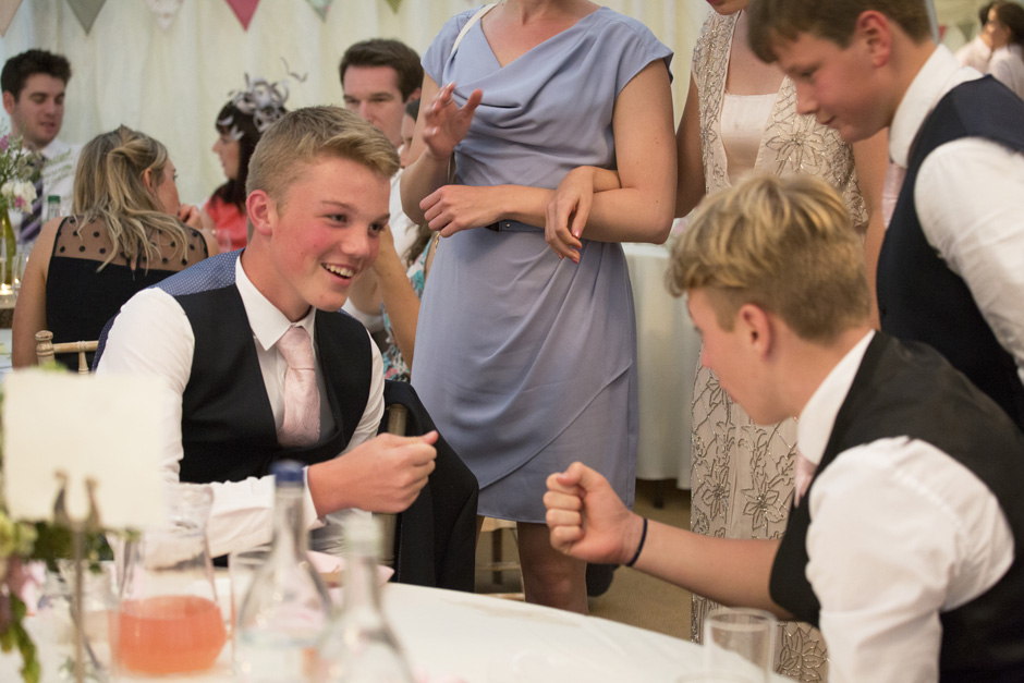 boys playing 'rock paper scissors' at table during wedding breakfast at Smarden home marquee in Kent