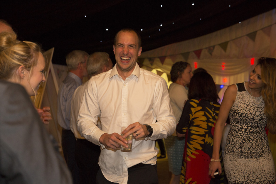 male wedding guest laughing at evening wedding reception in Smarden village home marquee in Kent