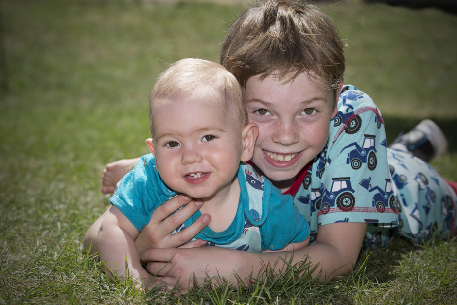little boy with baby brother on their tummies in Tonbridge, Kent