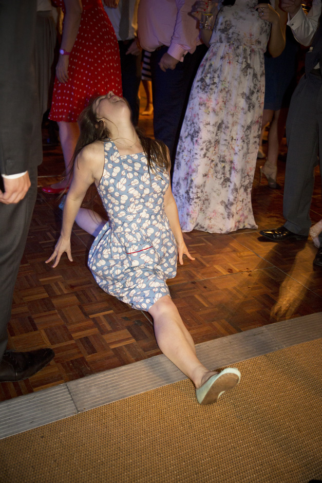 female wedding guest doing the splits on the dance floor during evening wedding reception at Smarden village home marquee in Kent