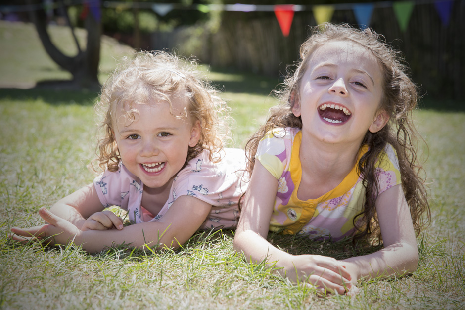 little sisters laughing together at summer fete in Tonbridge, Kent