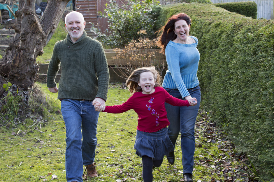little girl running with her smiling parents in her garden in Tonbridge, Kent