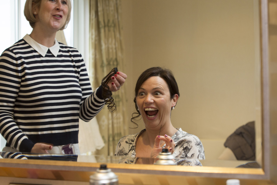 bride pulling a funny face in the mirror holding a hair pin during bridal prep at Dale Hill Hotel in Ticehurst, East Sussex