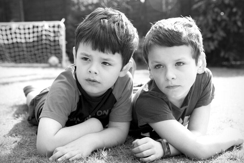 little brothers sitting on their tummies in their garden in Tonbridge, Kent