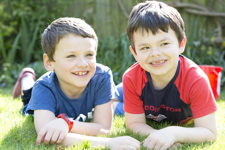 little brothers sitting together on their tummies in their garden in Tonbridge, Kent