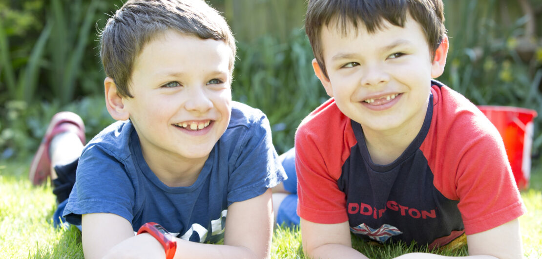 two boys sitting on their tummies smiling in their garden in Tonbridge, Kent