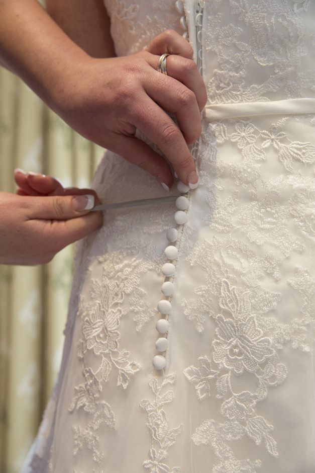 bridesmaid fastening buttons on wedding dress using hook during bridal prep at Dale Hill Hotel in Ticehurst, East Sussex