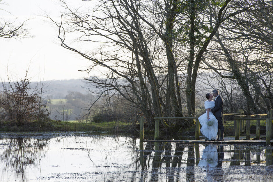 bride and groom in a romantic embrace by the lake at Swallows Oast in Ticehurst in East Sussex