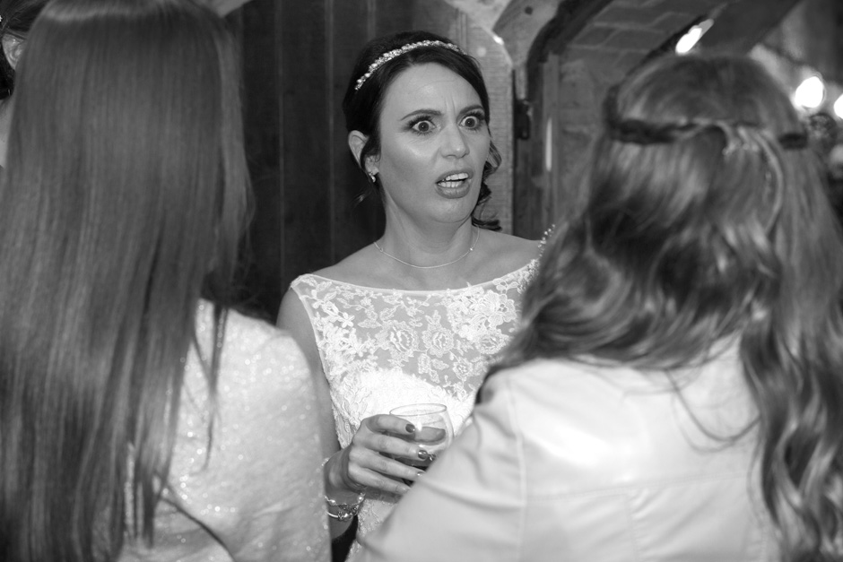 bride looking shocked chatting to female wedding guests at Swallows Oast in Ticehurst, East Sussex