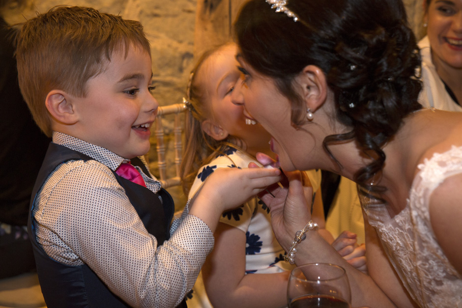 bride playing with little boy at Swallows Oast wedding reception in Ticehurst, East Sussex