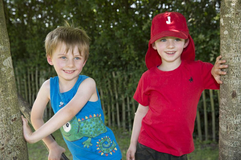 twin boys standing in a tree in Tonbridge, Kent