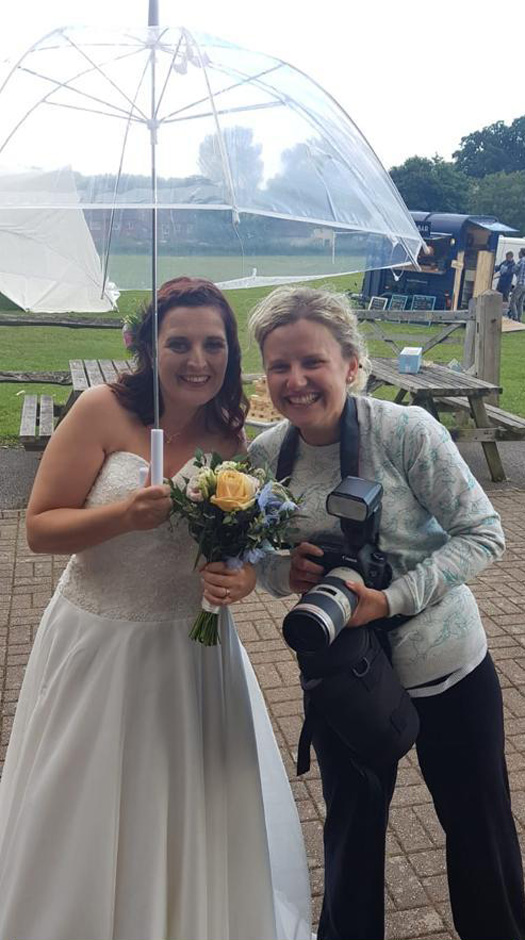 Victoria Green wedding photographer with bride in the rain, outside Uxbridge Village Hall