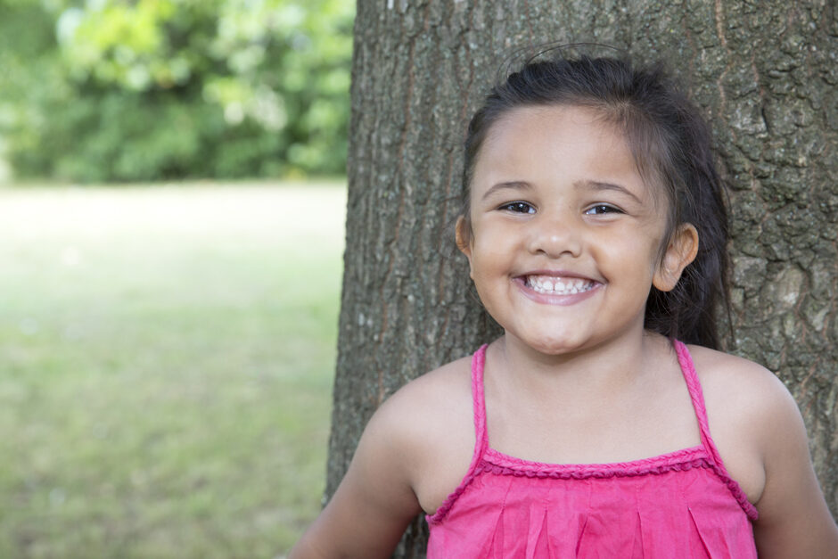 four year old indian girl portrait standing by tree in Tonbridge, Kent.