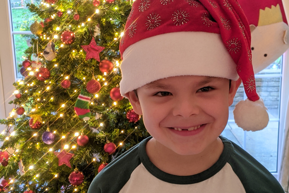 Little boy with santa's hat on standing by the christmas tree