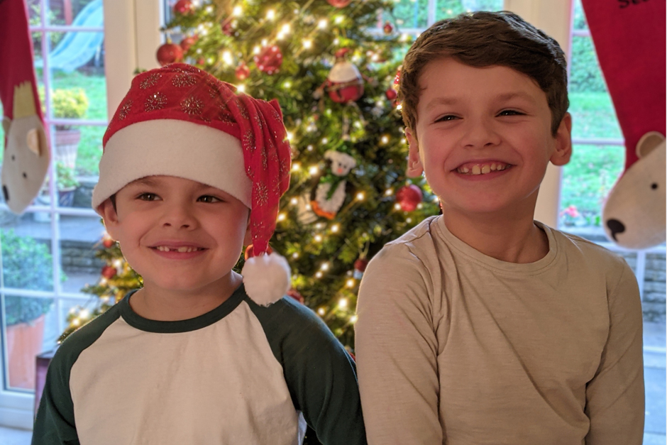 two little boys standing by the christmas tree laughing