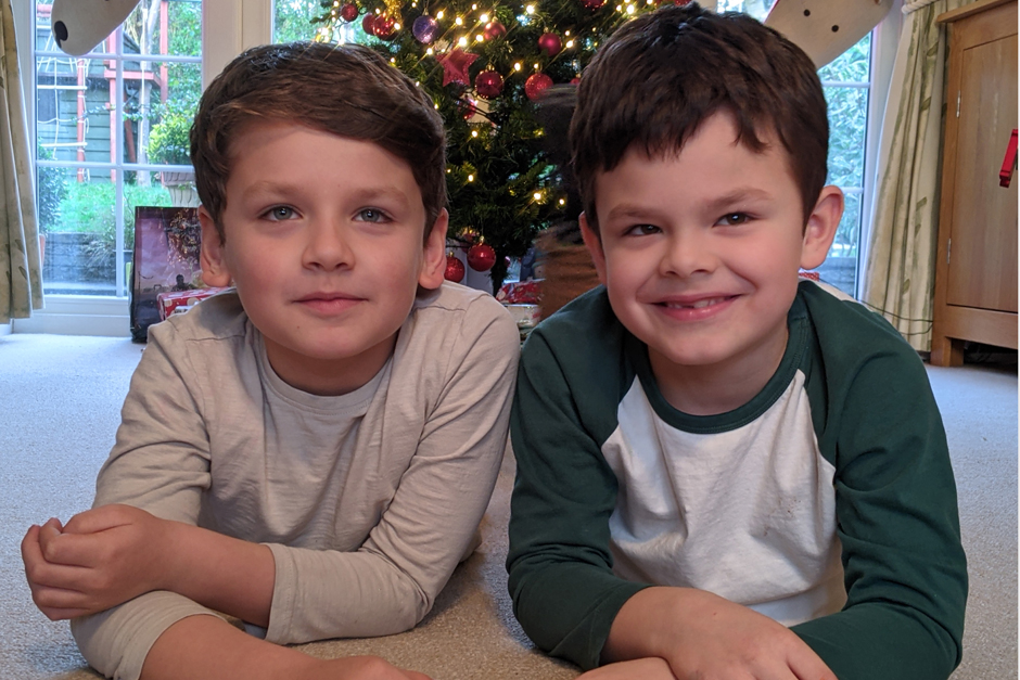 two little boys sitting on their tummies in front of the christmas tree