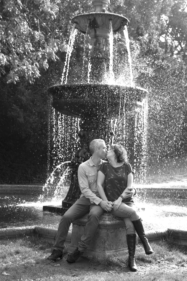 Engagement shoot with couple sitting by water fountain at Dunorlan Park, Tunbridge Wells in Kent