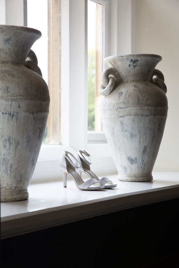 bride's shoes taken on shelf next to large ceramic pots at Wotton House in Dorking, Surrey
