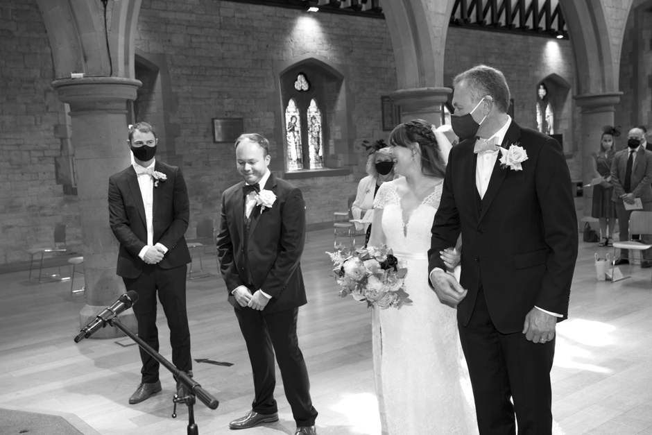 Bride and groom laughing arriving at the front of the aisle at St Stephen's church wedding in Tonbridge, Kent