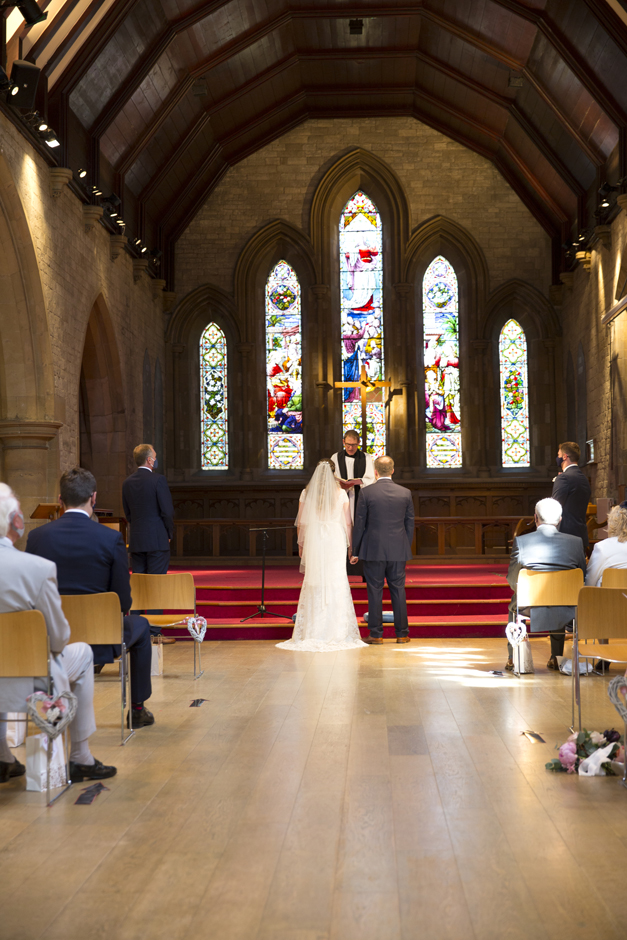 Bride and groom from behind standing at St Stephen's Church wedding in Tonbridge, Kent