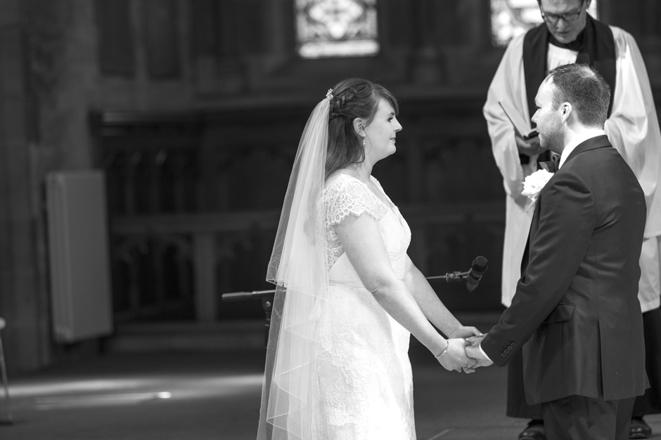 Close of bride and groom holding hands and exchanging vows at St Stephen's Church in Tonbridge, Kent
