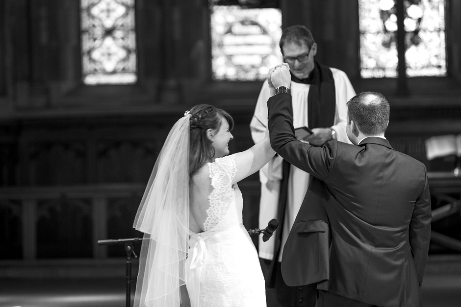 Bride and Groom holding and raising hands in the air at St Stephen's Church wedding in Tonbridge, Kent