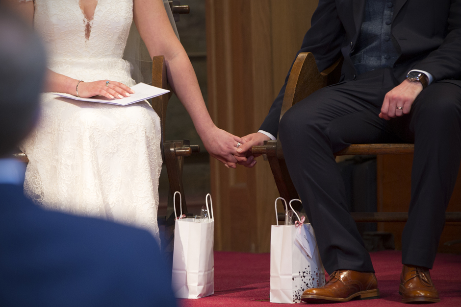 Close-up of bride and groom holding hands during wedding ceremony at St Stephen's Church in Tonbridge, Kent