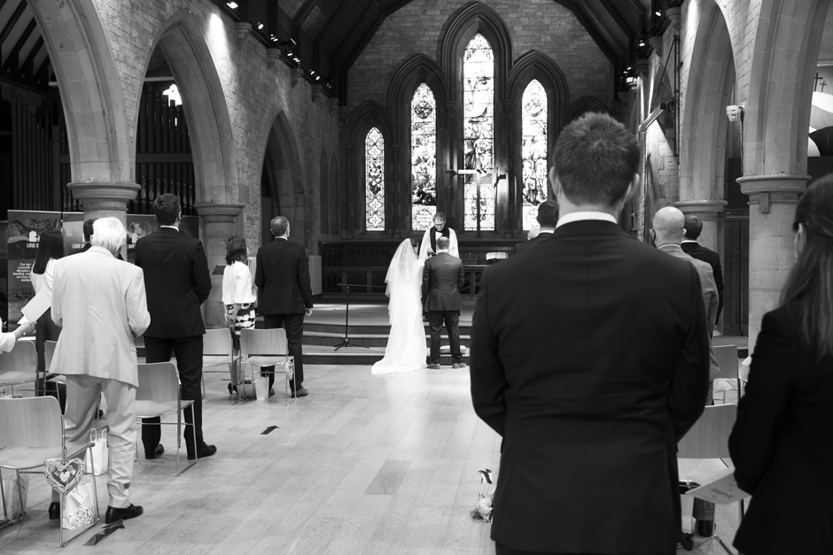 Guests and bride and groom from behind during wedding ceremony at St Stephen's wedding ceremony in Tonbridge, Kent