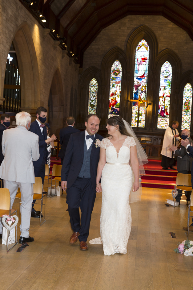 Bride and groom laughing walking up the aisle at St Stephen's Church in Tonbridge, Kent