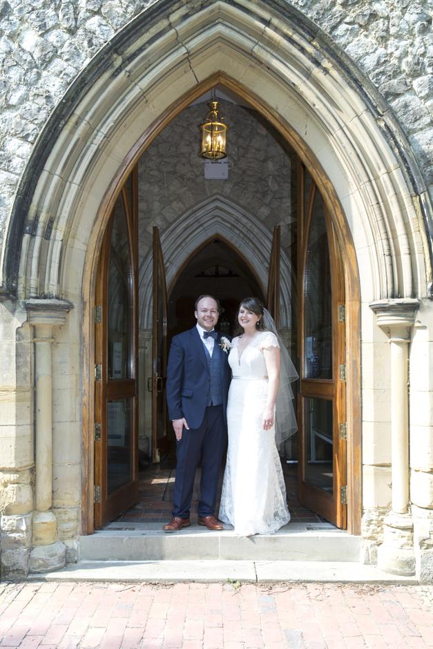 Bride and Groom standing under arched entrance doorway of St Stephen's Church in Tonbridge, Kent