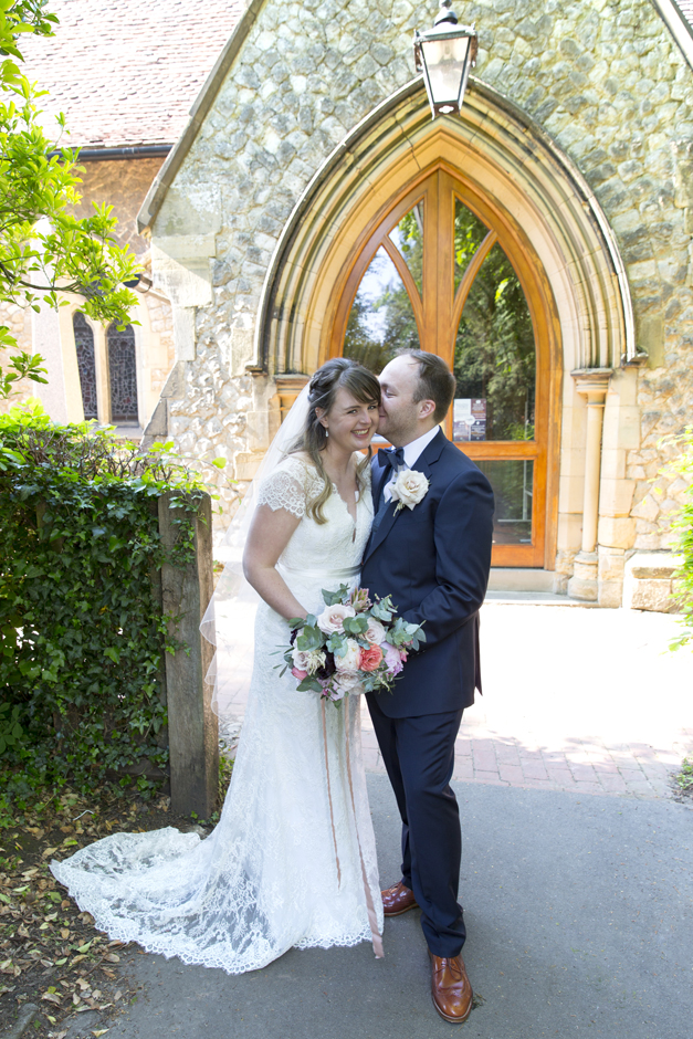 Bride laughing with groom during portrait outside St Stephen's church wedding in Tonbridge, Kent