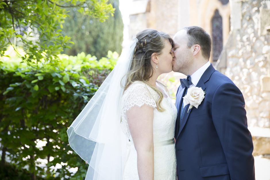 Bride and Groom kissing wedding portrait outside of St Stephen's Church in Tonbridge, Kent
