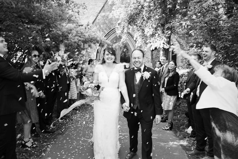 Bride and Groom laughing walking through confetti tunnel outside St Stephen's Church in Tonbridge, Kent
