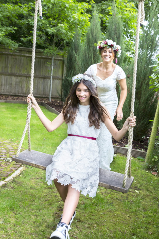 Bridesmaid on swing and bride pushing the swing laughing captured by Kent wedding photographer Victoria Green