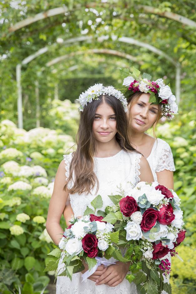 Bride and Bridesmaid under rose arch holding silk flower bouquets, captured by Kent wedding photographerVictoria Green