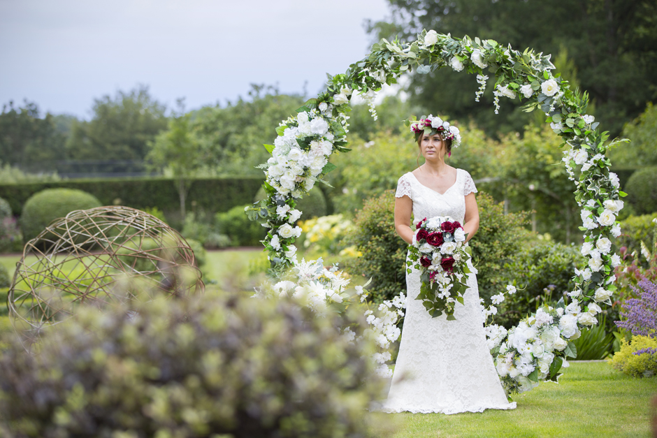 Silk flower moongate (by Lily & Rose) with bride standing in the middle captured by Kent wedding photographer Victoria Green