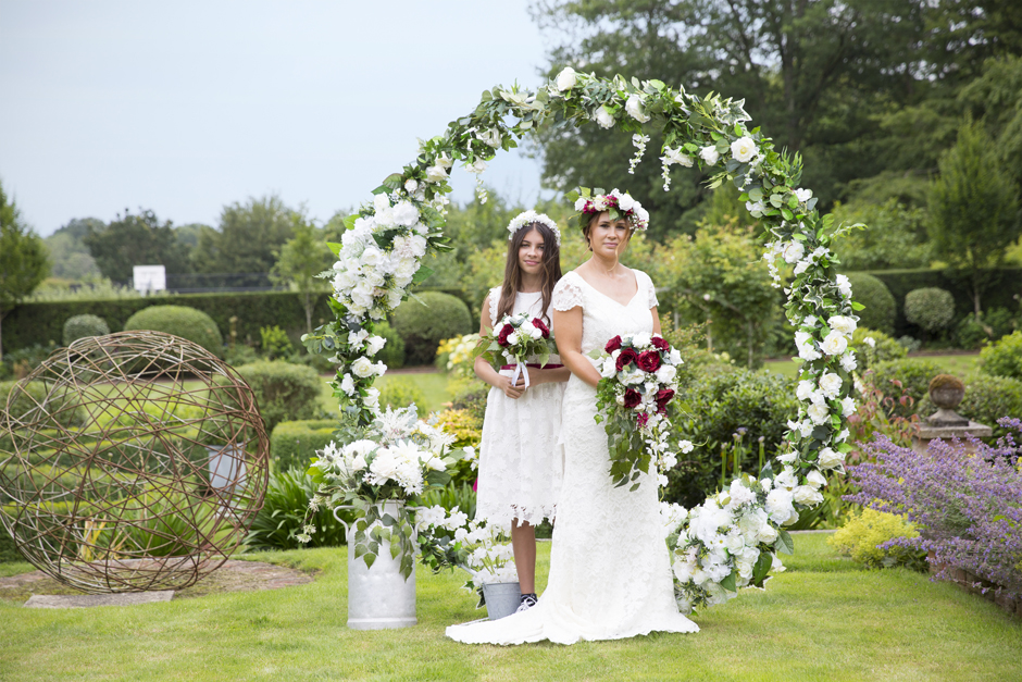 Bride and bridesmaid standing in the middle of a silk flower moongate (by Heather at Lily & Rose) captured by Kent wedding photographer Victoria Green